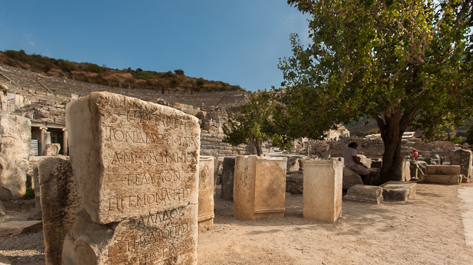 Stone pillar with inscriptions; 25,000 seat theatre in the background.