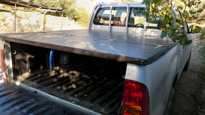 Truck tray cover: timber and oriented-strand board covered in black vinyl.